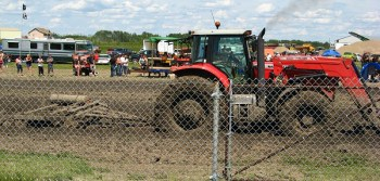 Tractor cultivating the mud pits at the 2012 Pilot Butte Mud bog event.