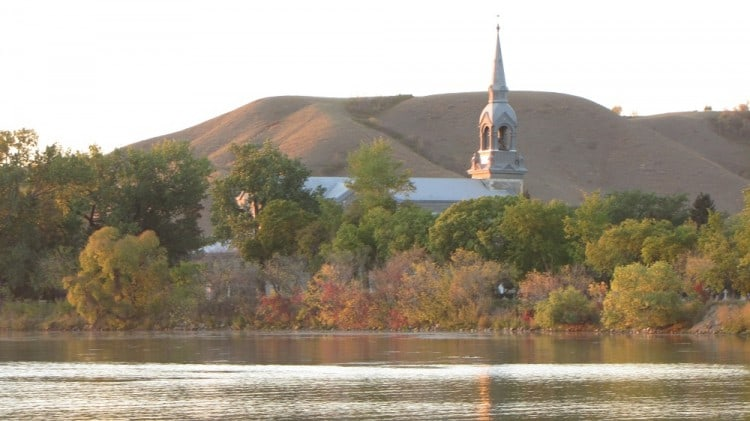 Sacred Heart Roman Catholic Church in the town of Lebret, SK, viewed from Mission Lake at dusk.