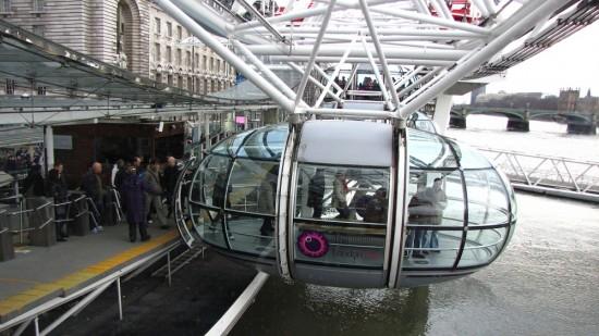 Passengers boarding the London Eye as it revolves slowly.