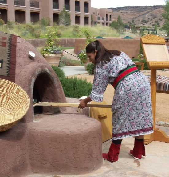 Pueblo Woman using traditional oven at Indian Pueblo Cultural Center