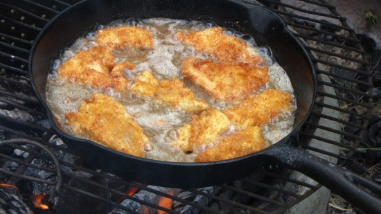 Frying walleye in a cast iron pan over an open fire.