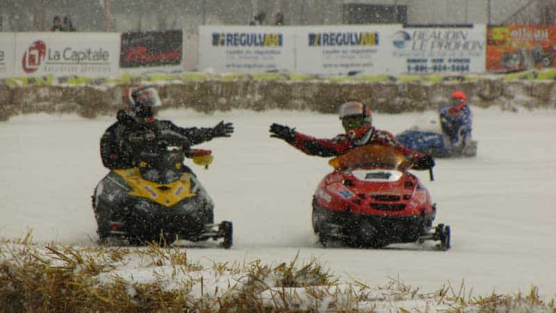 Two snowmobiles at the end of a race on a snowy day in Valcourt, Quebec, at the Grand Prix Ski-Doo de Valcourt.