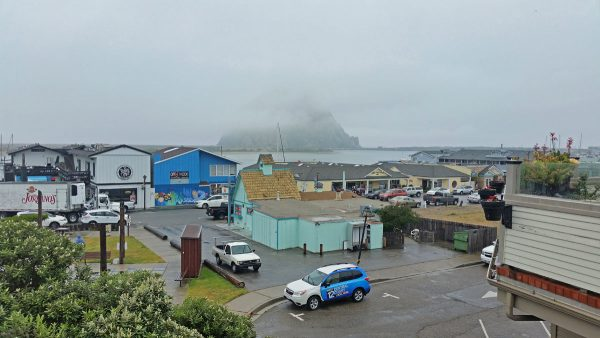 City of Morro Bay, California, houses and shore, with Morro Rock shrouded in mist in the distance.