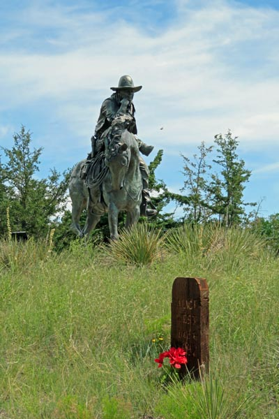 Boot Hill Trail Boss statue with a grave and flowers.