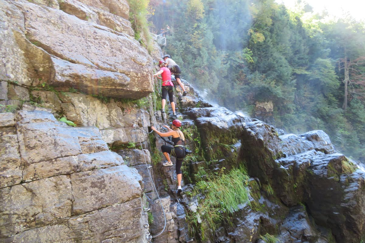 Climbing up the rocks on the via ferrata at Canyon Sainte-Anne