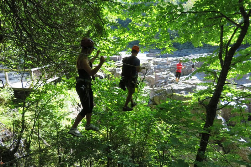 First steps on the Canyon Sainte-Anne via ferrata wire over rushing water.