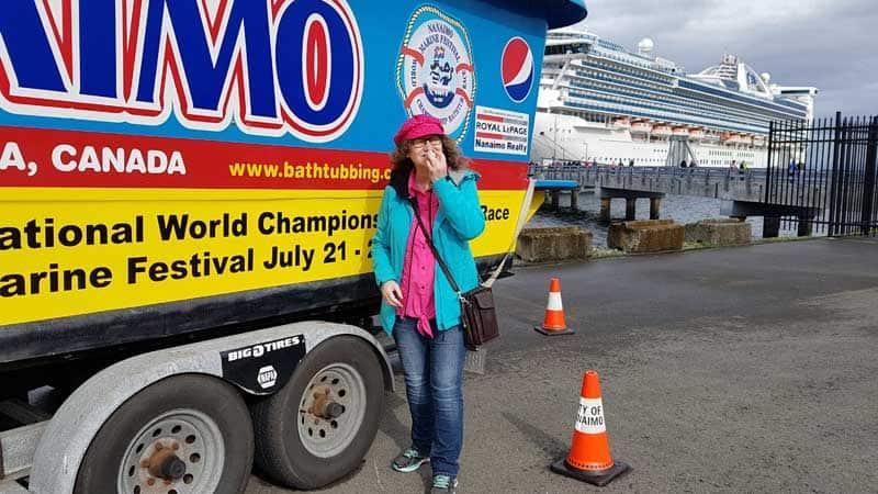 Linda Aksomitis eating Nanaimo bars under the Nanaimo sign at the cruise ship terminal.