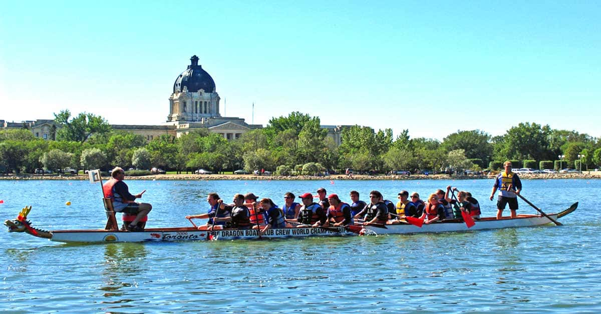 Dragon boats on Wascana Lake in front of the Saskatchewan Legislature Building.
