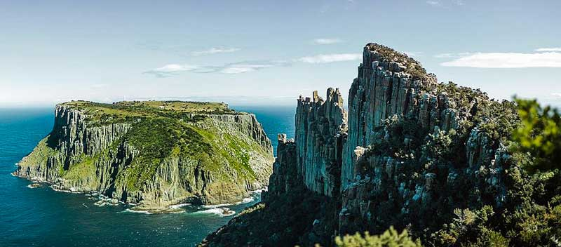 Dramatic dolorite rock formations on the Three Capes Track hike in Tasmania, Australia.