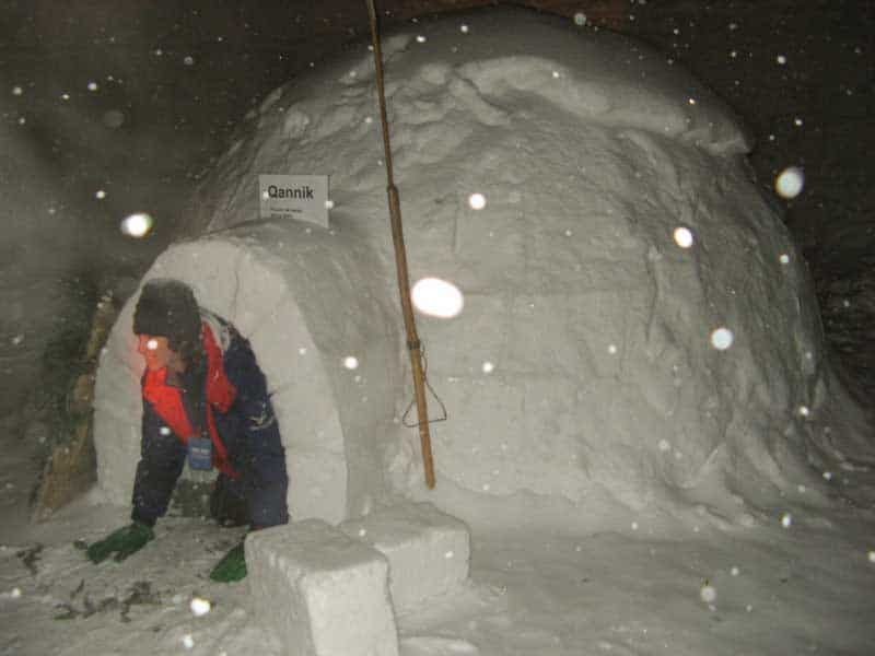 Crawling out of an igloo on a Quebec winter adventure.
