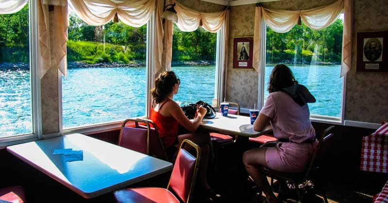 Travelers relaxing below deck in the comfortable dining room on the Lewis & Clark Riverboat.