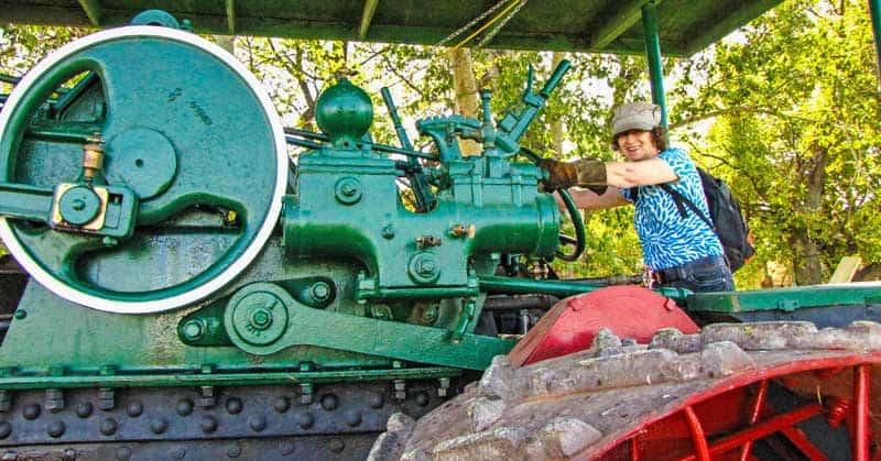 Linda Aksomitis on a vintage farm steam tractor.