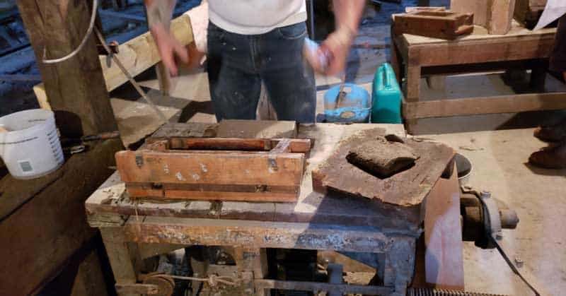 Volunteer demonstrating the sliding box form used to shape bricks from the clay.