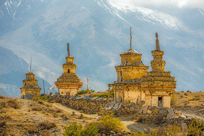 Traditional old Buddhist stupas on Annapurna Circuit Trek in Himalaya mountains, Nepal. — Photo by mazzzur