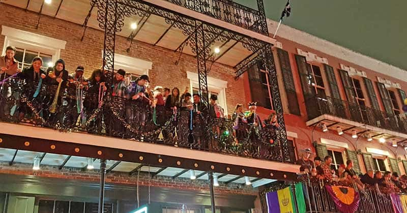 People throwing beads from the balconies on Bourbon Street.