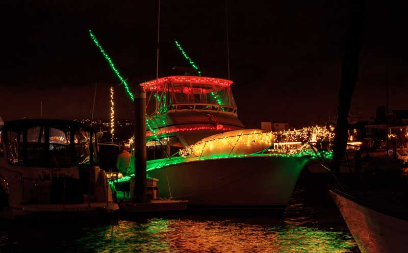 Colorful holiday lights on sailboats and ships in the Balboa Harbor for the Newport Beach Christmas Boat Parade during winter in California. — Photo by YAYImages