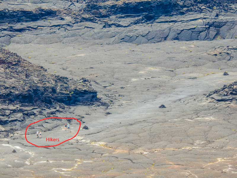 Things to do in Hilo - Hikers in the once molten lake of lava in Volcanoes National Park in Hawaii.